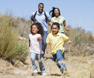 an african american family running outdoors smiling