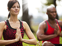 a white women and african man relaxing doing yoga