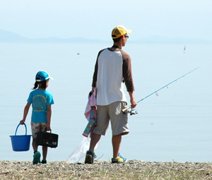 a father and son walking along the beach with fishing gear