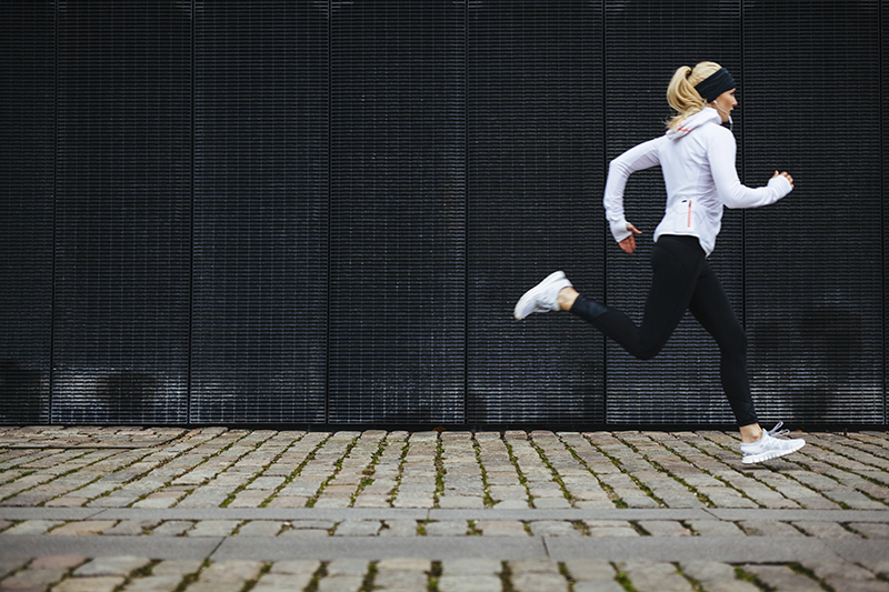 a women wearing a white ahtletic jacket and black tights running on a stone block path